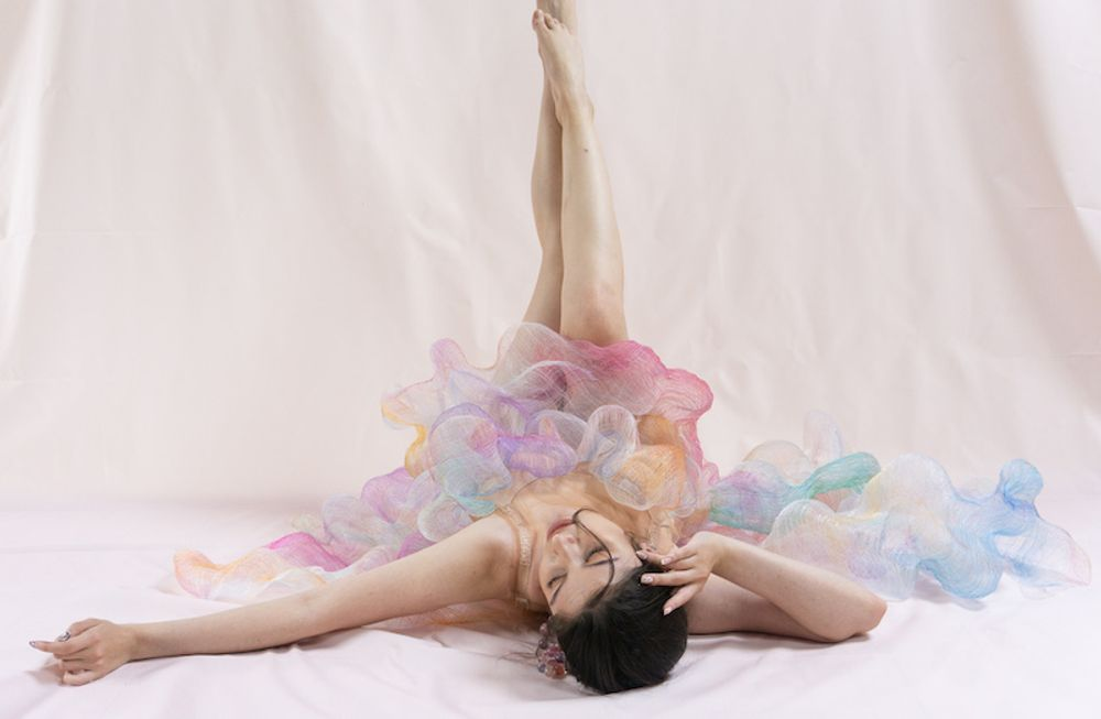 A model wears a pastel chiffon textile dress. She is lying on the floor, arms stretched out beside her and her legs in the air, replicating a balletic pose
