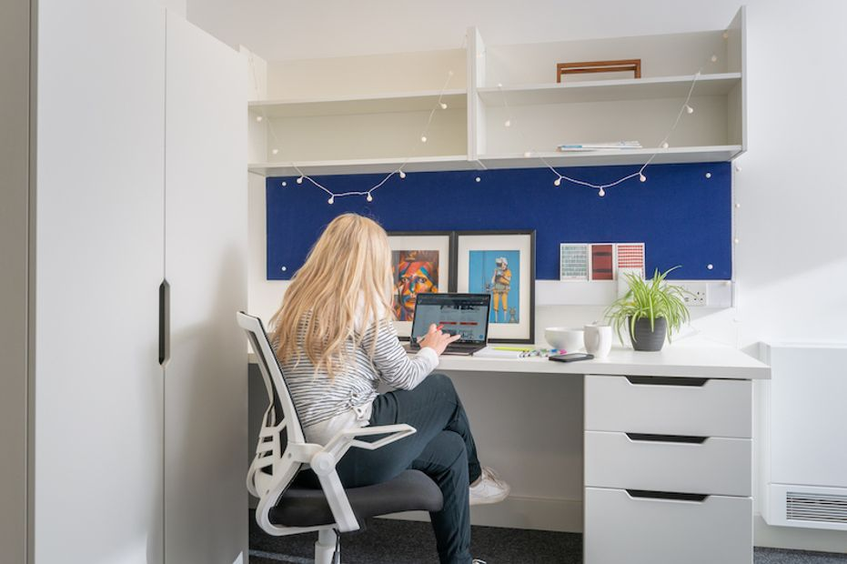 A student working at her desk in her bedroom at Epsom accommodation Bradford House
