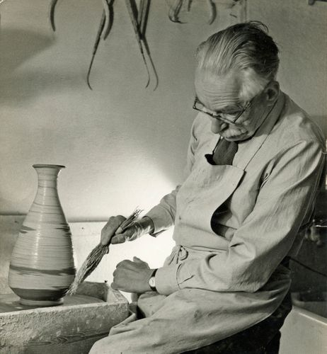 Bernard Leach working at the wheel and applying decoration to a stoneware pot  with a hakeme (twig) brush at St Ives, 1963. From the Bernard Leach archive at the Crafts Study Centre, BHL/7095.